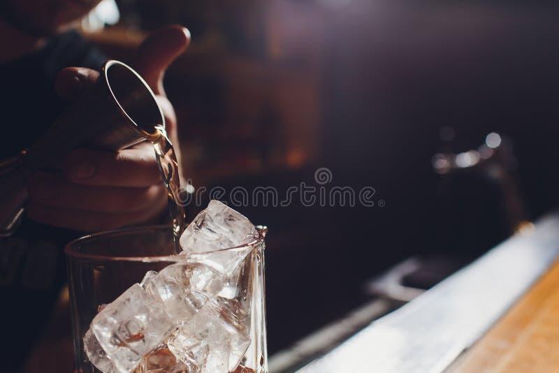 Μπάρμαν στο πουκάμισο και ποδιά που κατασκευάζει ένα οινοπνευματώδες ποτό με τον πάγο σε ένα γυαλί κοκτέιλ στοκ φωτογραφίες