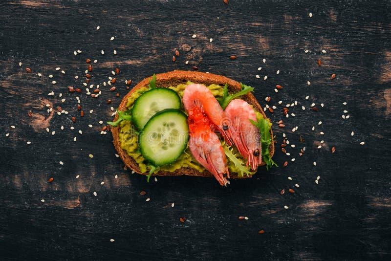 Μπέργκερ, σάντουιτς με γαρίδες, αβοκάντο, χαβιάρι και αγγούρι Σε ξύλινο φόντο στοκ φωτογραφίες