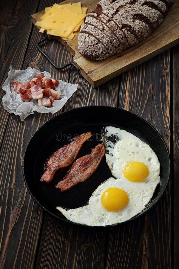 Μπέϊκον και αυγά στο ξύλινο καφετί υπόβαθρο ψωμί, τυρί στοκ εικόνα