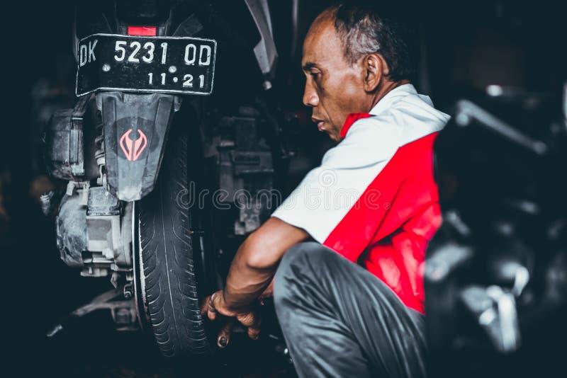 ΜΠΑΛΙ, ΙΝΔΟΝΗΣΙΑ - 17 ΜΑΐΟΥ 2018: Αντικατάσταση ροδών μοτοσικλετών, εγκατάσταση στο γκαράζ Επισκευή μηχανικών δίκυκλων μοτοποδηλά στοκ φωτογραφίες με δικαίωμα ελεύθερης χρήσης