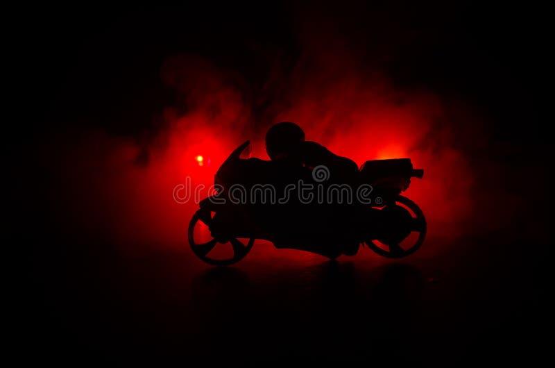 Μπαλτάς μοτοσικλετών υψηλής δύναμης Ομίχλη με τα backlights στο υπόβαθρο με τον αναβάτη ατόμων τη νύχτα στοκ εικόνες