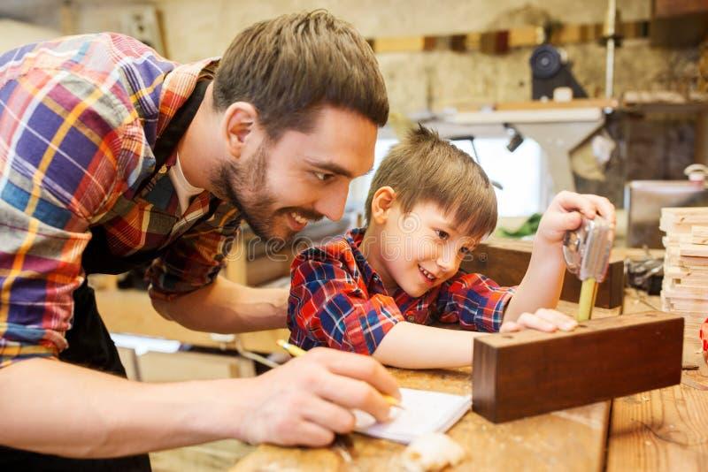 Μπαμπάς και γιος με τον κυβερνήτη που μετρά τη σανίδα στο εργαστήριο στοκ εικόνα με δικαίωμα ελεύθερης χρήσης