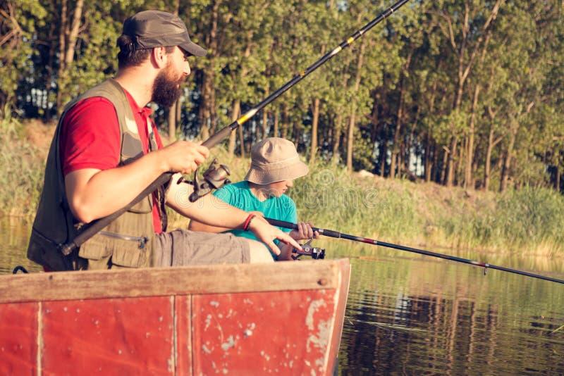 Μπαμπάς και γιος που αλιεύουν στη λίμνη στην επαρχία, αυτοί συνεδρίαση με την αλιεία των ράβδων στοκ φωτογραφία