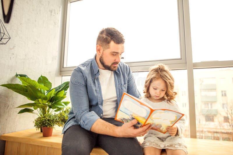Μπαμπάς και κόρη που διαβάζουν ένα βιβλίο στο σπίτι στοκ εικόνες