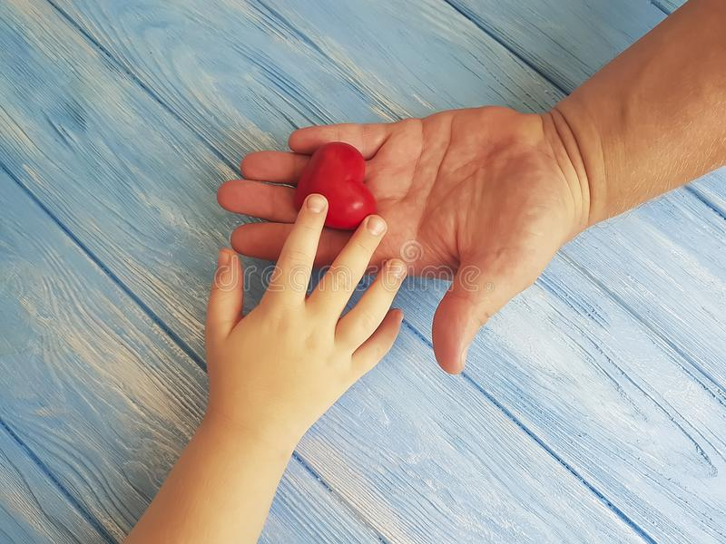 Μπαμπάς και παιδί χεριών ημέρας πατέρων ` s που δίνουν στη δημιουργική εκμετάλλευση την ευγνώμονα καρδιά σε ένα μπλε ξύλινο υπόβα στοκ εικόνες