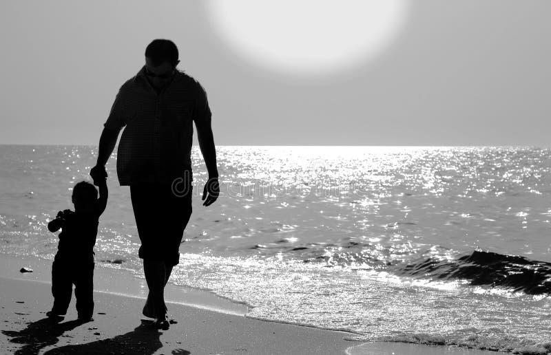 Μπαμπάς και παιδί στην παραλία στο ηλιοβασίλεμα στοκ φωτογραφίες