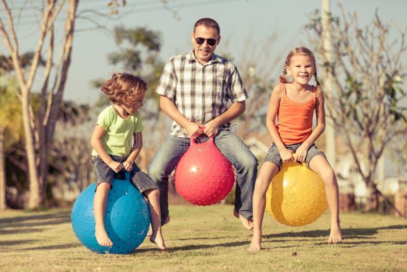 Μπαμπάς και παιδιά που παίζουν στο χορτοτάπητα στοκ φωτογραφίες