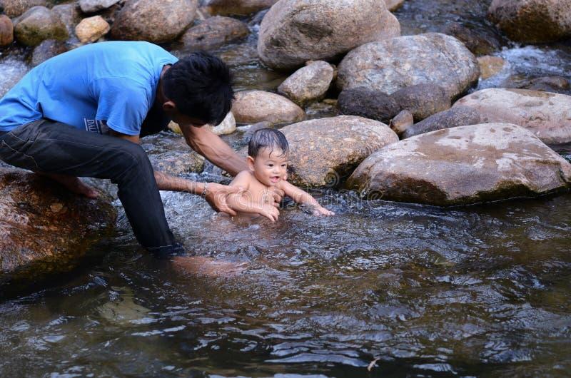 Μπαμπάς και χαμογελώντας αγόρι που κολυμπούν στον ποταμό στοκ εικόνες