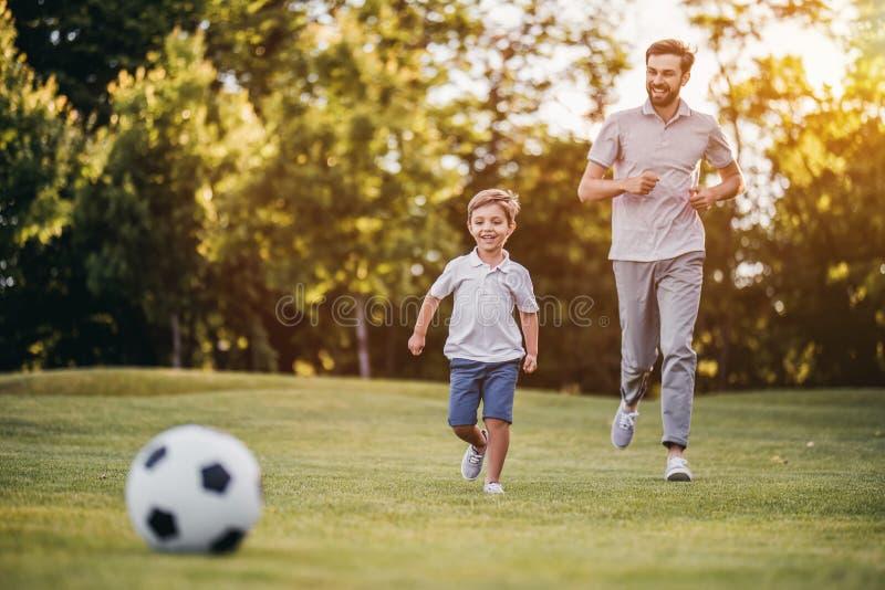 Μπαμπάς με το παίζοντας μπέιζ-μπώλ γιων στοκ φωτογραφία
