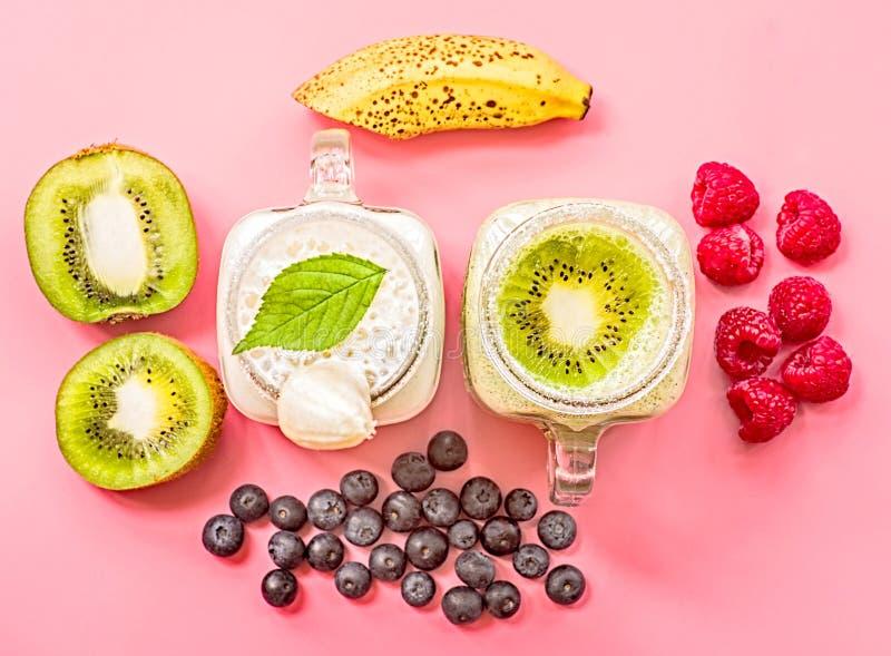 Μπανάνα δύο και ακτινίδιο milkshakes στα βάζα κτιστών με creme στην κορυφή που διακοσμείται με τα ακτινίδια, τις μπανάνες, τα σμέ στοκ φωτογραφία