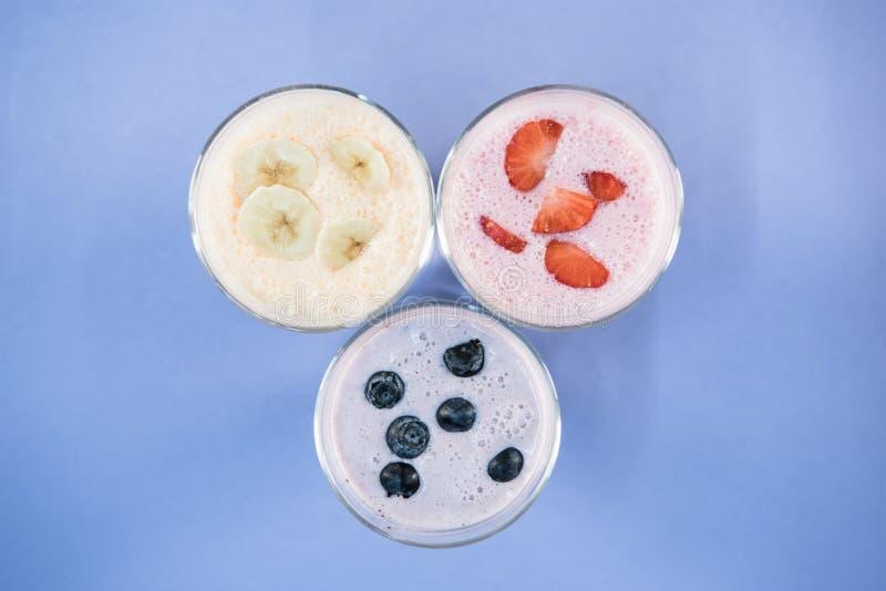 Μπανάνα και μούρο milkshakes στα γυαλιά στην μπλε επιφάνεια στοκ φωτογραφίες