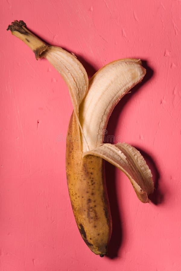 Μπανάνα προσδιορισμού κιτς που ξεφλουδίζεται σε ένα ρόδινο υπόβαθρο στοκ εικόνες