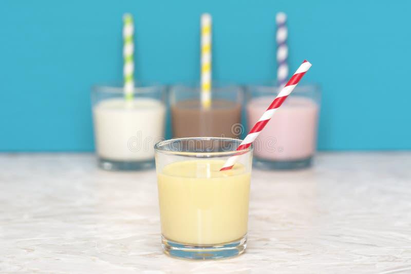 Μπανάνα milkshake μπροστά από μια σειρά αρωματικός milkshakes στοκ εικόνα με δικαίωμα ελεύθερης χρήσης