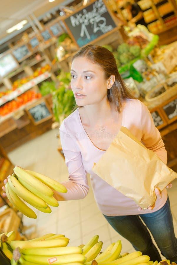 Μπανάνες γυναικείας αγοράς που κρατούν την τσάντα εγγράφου στοκ φωτογραφία