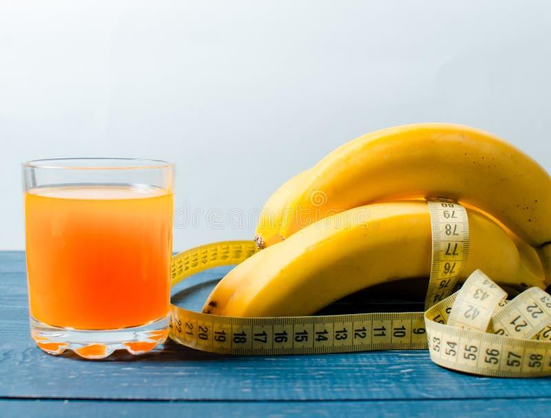 Μπανάνες και χυμός από πορτοκάλι σε ένα ξύλινο υπόβαθρο Τρόφιμα για το βάρος στοκ φωτογραφίες με δικαίωμα ελεύθερης χρήσης