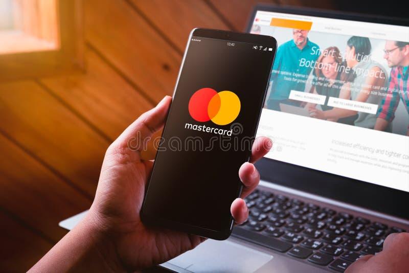 Μπανγκόκ, Ταϊλάνδη - 6 Αυγούστου 2019: Χέρια που κρατούν Smartphone με Mastercard την οθόνη λογότυπων και Mastercard τον ιστοχώρο στοκ εικόνα με δικαίωμα ελεύθερης χρήσης