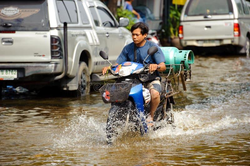 Μπανγκόκ, Ταϊλάνδη - 5 Νοεμβρίου 2011: Ένα άτομο παράδοσης οδηγεί μια μοτοσικλέτα σε μια πλημμυρισμένη οδό μετά από τη καταρρακτώ στοκ εικόνα με δικαίωμα ελεύθερης χρήσης