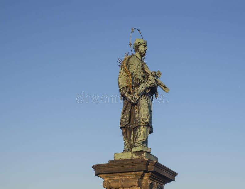 Μπαρόκ άγαλμα Αγίου John Nepomuk με χρυσό crucifix εκμετάλλευσης φωτοστεφάνου αστεριών με το Ιησούς Χριστό στη γέφυρα του Charles στοκ εικόνες