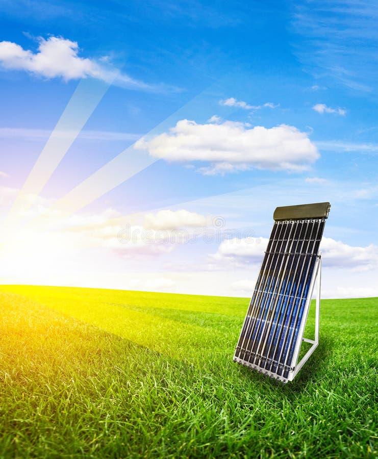 Μπαταρία ηλιακού πλαισίου στον τομέα με τον πράσινους μπλε ουρανό χλόης και τις ακτίνες του ήλιου στοκ εικόνα