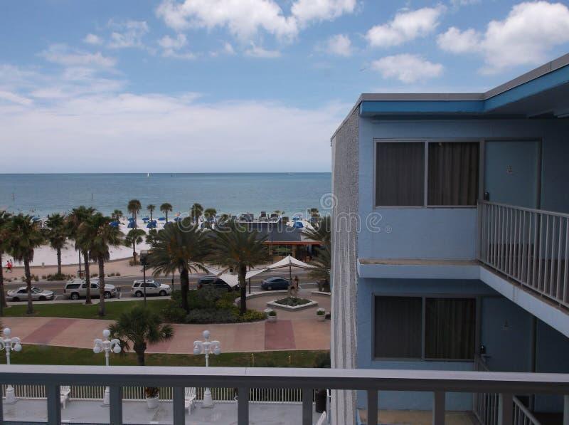Μπαλκόνι ξενοδοχείων πέρα από να φανεί φοίνικες και ωκεανός στοκ εικόνες