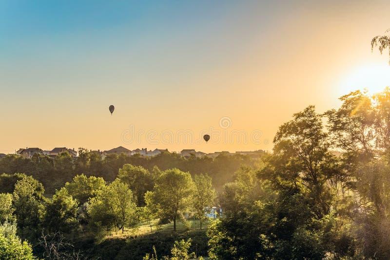 Μπαλόνια ζεστού αέρα πέρα από τις στέγες των προαστιακών σπιτιών λαμβάνοντας υπόψη το χαμηλό ήλιο βραδιού backlight στοκ εικόνα