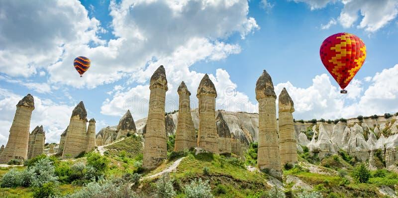 Μπαλόνια ζεστού αέρα που πετούν πέρα από την κοιλάδα αγάπης σε Cappadocia, Τουρκία στοκ εικόνες