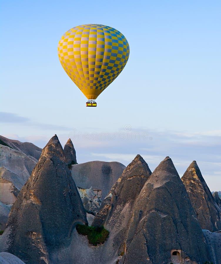 Μπαλόνι ζεστού αέρα που πετά πέρα από το τοπίο βράχου σε Cappadocia, Τουρκία στοκ εικόνα