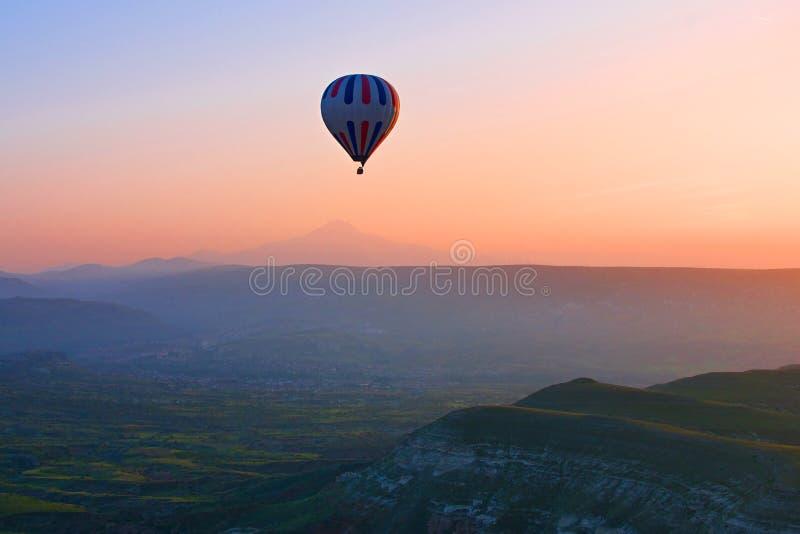 Μπαλόνι ζεστού αέρα που πετά στην ανατολή, Cappadocia, Τουρκία στοκ φωτογραφία