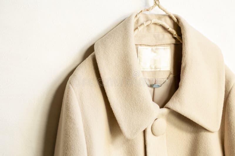 Μπεζ ένωση παλτών μαλλιού στην κρεμάστρα ενδυμάτων στο άσπρο υπόβαθρο στοκ φωτογραφία με δικαίωμα ελεύθερης χρήσης