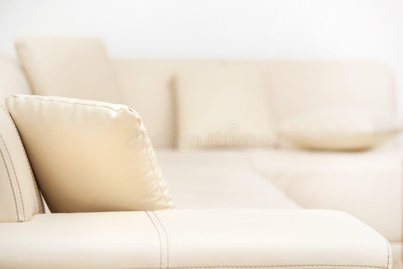Μπεζ καναπές δέρματος με τα μαξιλάρια στο καθιστικό στοκ εικόνες