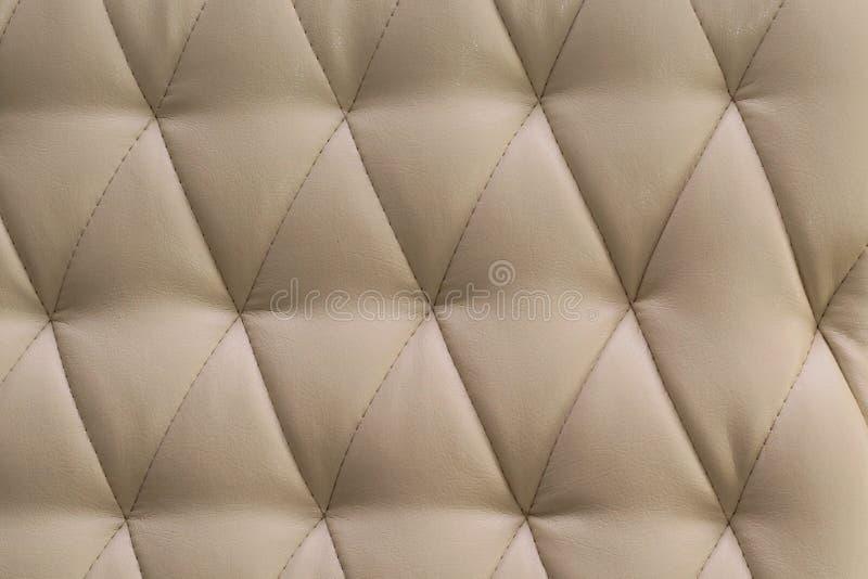 Μπεζ καναπές δέρματος με το υπόβαθρο σύστασης κουμπιών στοκ εικόνες με δικαίωμα ελεύθερης χρήσης