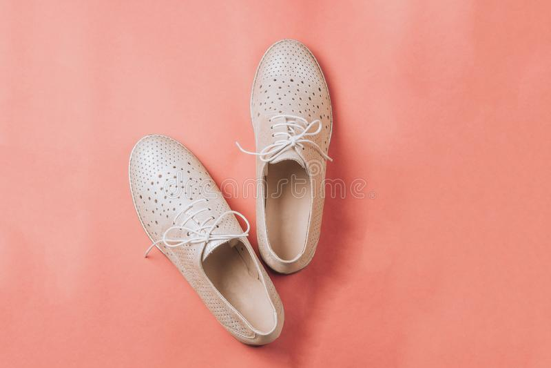 Μπεζ παπούτσια της Οξφόρδης μόδας στο ρόδινο υπόβαθρο στοκ φωτογραφία