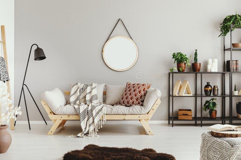 μπεζ τοίχος στο μοντέρνο καθιστικό boho με τον κομψό τάπητα καναπέδων και μανίας στοκ εικόνες