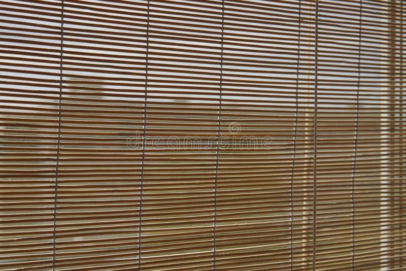 Μπεζ τυφλή ιαπωνική κουρτίνα μπαμπού στο παράθυρο στοκ εικόνες