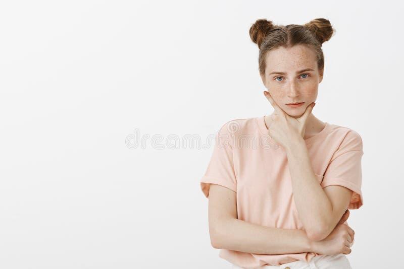 Μπερδεμένη έξυπνη και καθορισμένη γυναίκα σπουδαστής στη ρόδινη μπλούζα με τα κουλούρια hairstyle, το κράτημα των δάχτυλων και το στοκ φωτογραφία με δικαίωμα ελεύθερης χρήσης