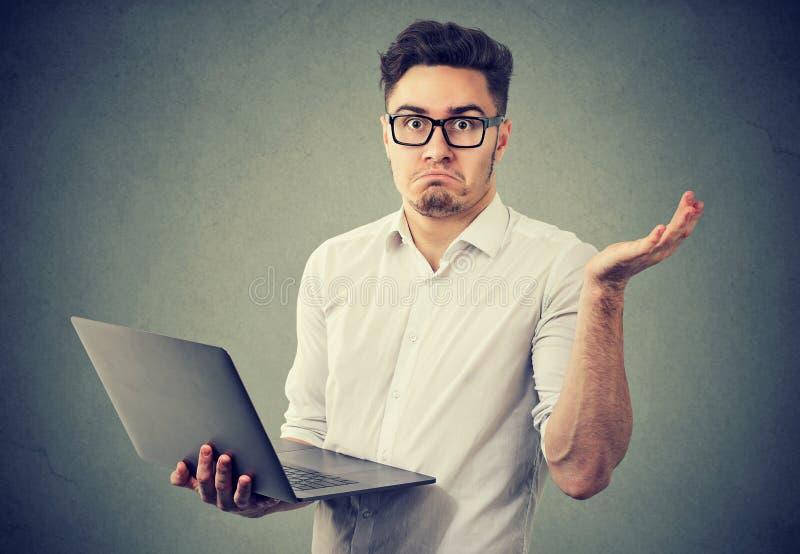 Μπερδεμένος νεαρός άνδρας με το lap-top στοκ φωτογραφία με δικαίωμα ελεύθερης χρήσης