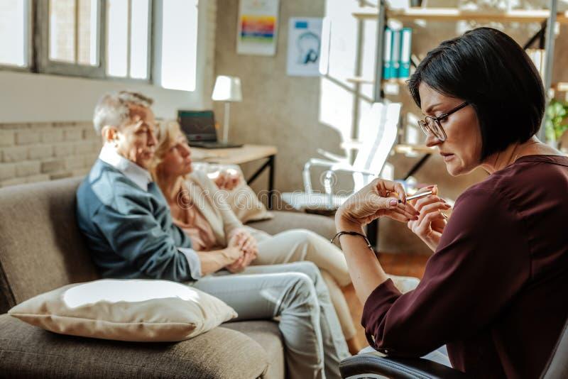 Μπερδεμένος ταραγμένος ψυχοθεραπευτής στα σαφή γυαλιά που εξετάζει τα προβλήματα στοκ εικόνα