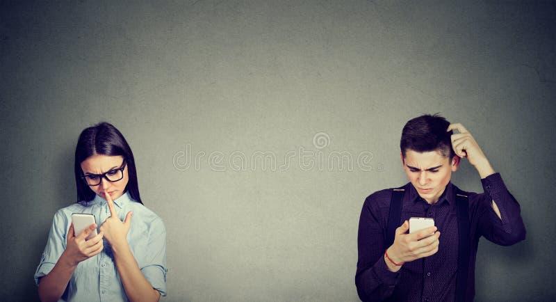 Μπερδεμένοι άνδρας και γυναίκα που εξετάζουν το κινητό τηλέφωνο στοκ εικόνες