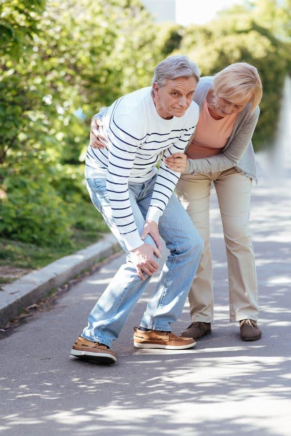 Μπερδεμένος συνταξιούχος που αισθάνεται τον πόνο στο γόνατο υπαίθρια στοκ φωτογραφία