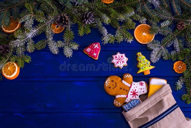Μπισκότα δέντρων και μελοψωμάτων έλατου Χριστουγέννων στο μπλε ξύλινο BO στοκ εικόνες