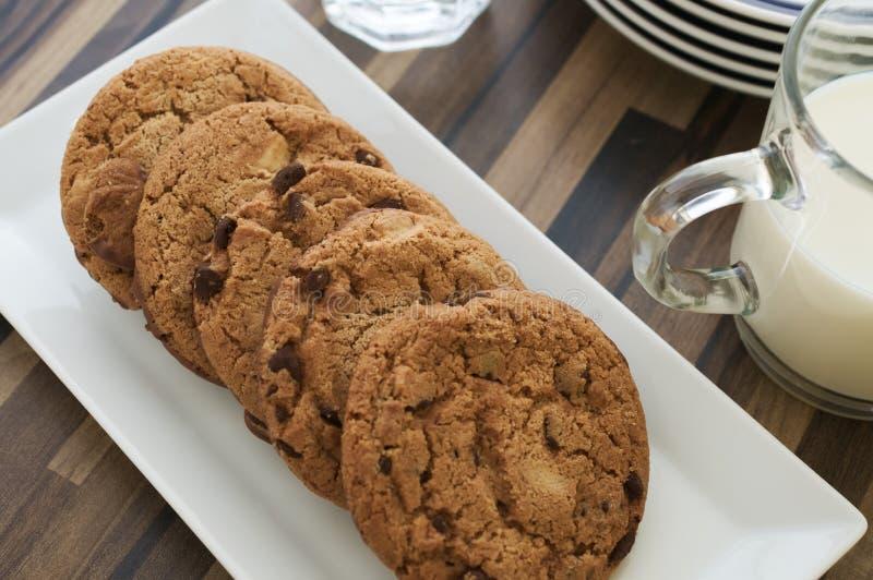 Μπισκότα και γάλα τσιπ σοκολάτας στο σκοτεινό ξύλινο πίνακα στοκ φωτογραφίες