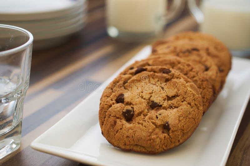 Μπισκότα και γάλα τσιπ σοκολάτας στο σκοτεινό ξύλινο πίνακα στοκ εικόνα