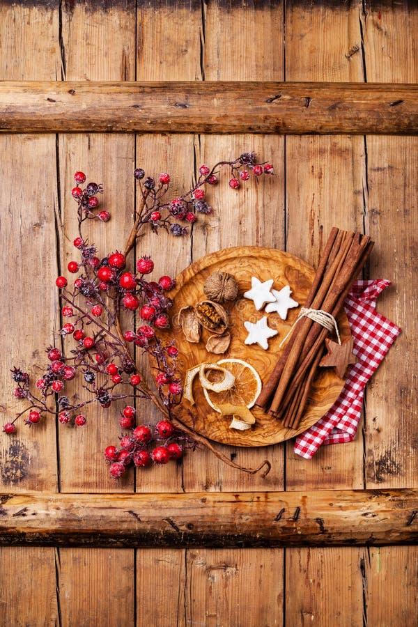 Μπισκότα, κανέλα και κλάδος Χριστουγέννων με τα κόκκινα μούρα στοκ εικόνες