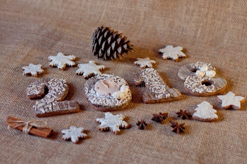 Μπισκότα μελιού διακοπών τυποποιημένα ως ξύλινους αριθμούς 2, 0, 1, 8 και αστέρια που βάζουν κοντά στους κώνους πεύκων, γλυκάνισο στοκ φωτογραφία