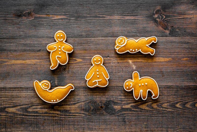 Μπισκότα μελοψωμάτων στη μορφή των asanas γιόγκας στη σκοτεινή ξύλινη τοπ άποψη υποβάθρου στοκ εικόνα με δικαίωμα ελεύθερης χρήσης