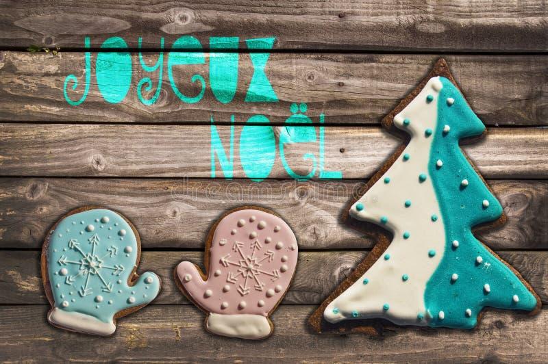 Μπισκότα μελοψωμάτων στο ξύλινα υπόβαθρο και το κείμενο joyeux noel στοκ φωτογραφίες