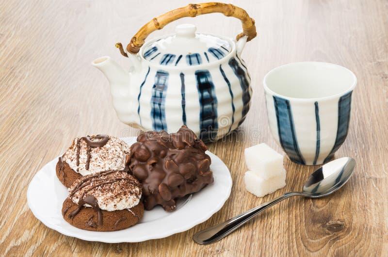 Μπισκότα με τη σοκολάτα και τα καρύδια, ριγωτό teapot, φλυτζάνι, άμορφο suga στοκ εικόνα