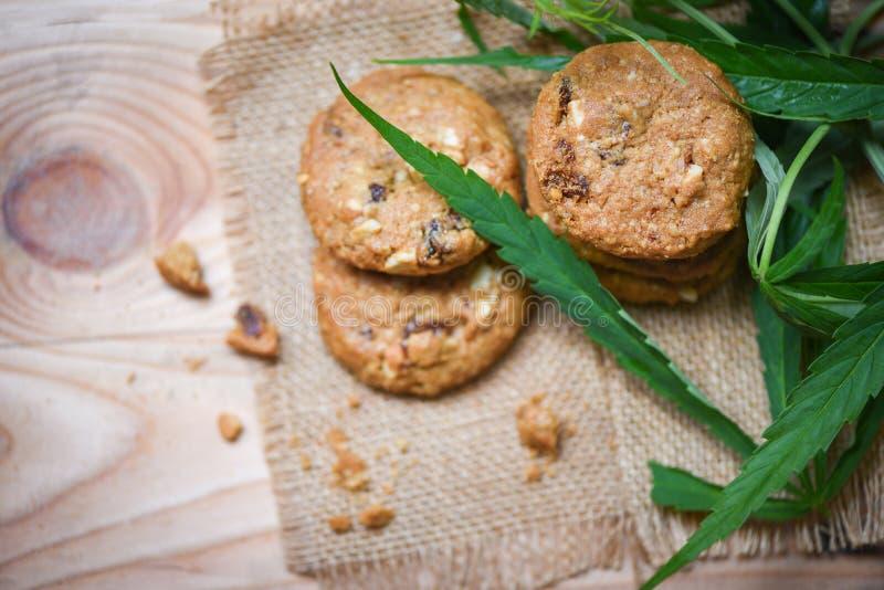 Μπισκότα με το χορτάρι μαριχουάνα φύλλων καννάβεων στο ξύλινο υπόβαθρο σάκων - πρόχειρο φαγητό τροφίμων καννάβεων για την υγεία στοκ εικόνα