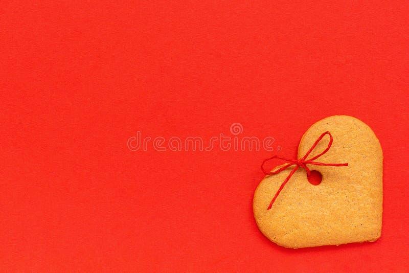 Μπισκότα πιπεροριζών καρδιά-που διαμορφώνονται που διακοσμούνται με ένα τόξο σε ένα κόκκινο υπόβαθρο Διαστημική κάρτα βαλεντίνων  στοκ φωτογραφία με δικαίωμα ελεύθερης χρήσης