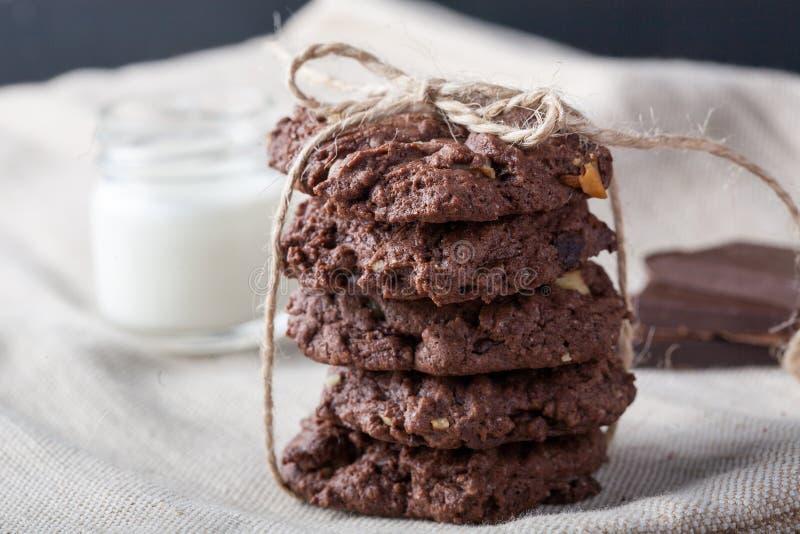 Μπισκότα σοκολάτας τσιπ σοκολάτας με τα κομμάτια σοκολάτας και γάλα σε ένα εκλεκτής ποιότητας υπόβαθρο Ευμετάβλητος αγροτικός κοι στοκ φωτογραφία με δικαίωμα ελεύθερης χρήσης